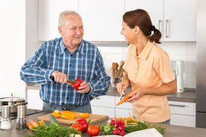 An image of two people peeling vegetables