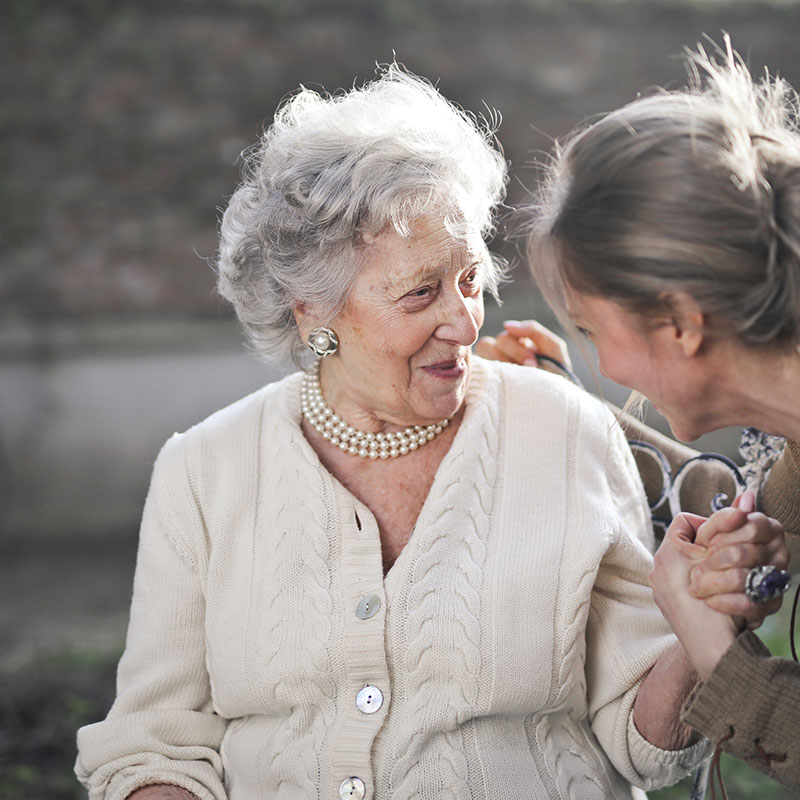 An aged care professional taking care of an elderly woman